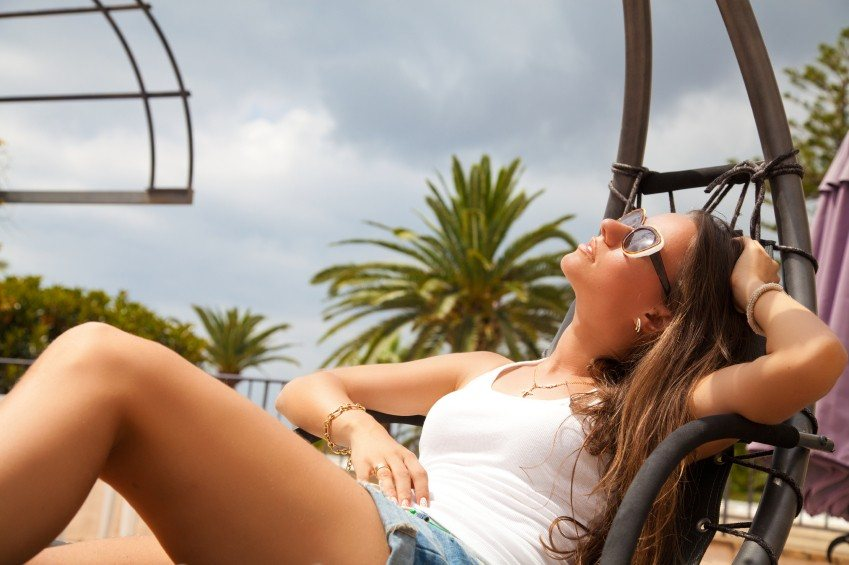 Beautiful young woman sunbathing at terrace, relaxing at luxury travel resort. Dreaming and thinking looking happy up smiling cheerful.